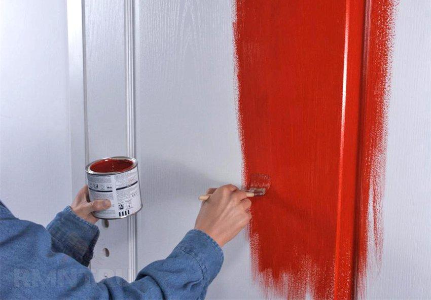 Мужчина красит старые окрашенные ранее межкомнатные двери